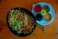 在可口泰国面条上看法,用在一金属盘子iver里面的四个调味汁一块白色板材在一张木桌里 图库摄影
