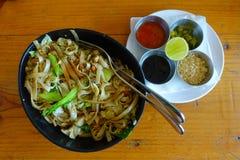 在可口泰国面条上看法,用在一金属盘子iver里面的四个调味汁一块白色板材在一张木桌里 免版税库存图片