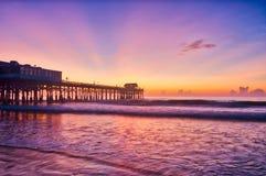 在可可粉海滩码头的日出在紫色蓝色和橙色 免版税库存照片