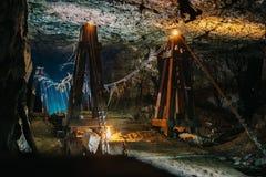 在可怕被放弃的地下石灰石矿洞的老木桥或隧道或者黑暗的走廊有神奇照明的 库存图片