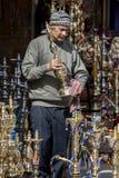 在可汗el Khal'ili义卖市场的一名店主在开罗,埃及在显示清洗他的一条水管去 库存照片