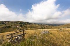 在可爱的农村风景前面的长木凳与小的村庄在Zabljak,狄那里克阿尔卑斯山脉, Montene附近的杜米托尔国家公园国家公园 免版税库存照片