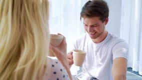 在可爱的夫妇饮用的早晨咖啡肩膀射击在轻的屋子里 股票视频