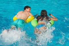 在可膨胀的圆环的夫妇在游泳池 免版税库存图片