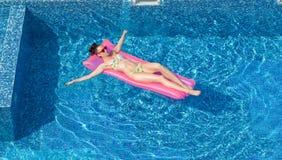 在可膨胀的床垫的有吸引力的妇女游泳在水池 免版税库存图片
