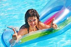 在可膨胀的海滩床垫的妇女游泳 库存照片