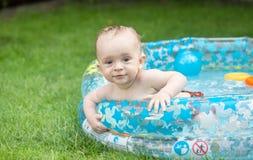 在可膨胀的游泳池的可爱的男婴游泳在ga 库存图片