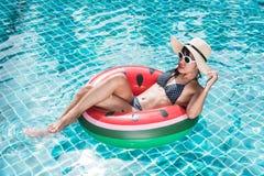 在可膨胀的西瓜的美丽的妇女比基尼泳装 库存图片