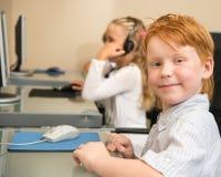 在台式计算机前面的一点红头发人男小学生 库存图片