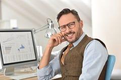 在台式计算机前面的中年人 免版税库存图片