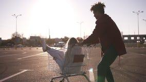 在台车在空的购物中心停车处,行家朋友的愉快的年轻夫妇骑马有美好时光在购物,夫妇以后  影视素材