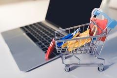 在台车的五颜六色的纸购物袋在膝上型计算机 顾客能买一切从办公室或家 库存图片
