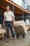 在台车的仓库工作者移动的箱子 免版税库存图片