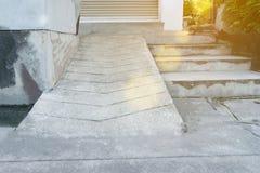 在台阶旁边的老具体倾斜道路有青苔污点的 免版税库存图片