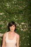 在叶子前面墙壁的妇女  免版税库存照片