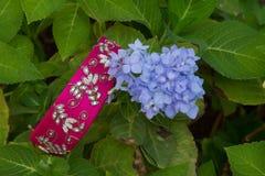 在叶子和花背景的一个传统手工制造印地安妇女` s发带  库存照片