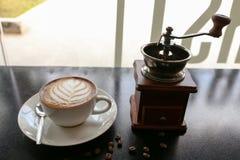 在叶子形状艺术的热的拿铁咖啡与在咖啡店的手磨床 库存照片