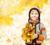 在叶子的秋天孩子,羊毛帽子的小孩 免版税库存照片