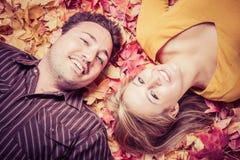 在叶子的年轻夫妇 免版税图库摄影