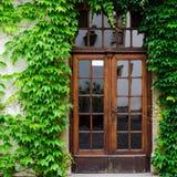 在叶子盖的墙壁的门 老房子概念 免版税图库摄影