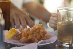 在吃在西班牙塔帕纤维布的鸡尾酒棍子的油煎的枪乌贼 免版税库存照片