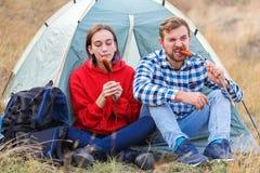 在吃开胃香肠的野餐的年轻夫妇 户外 免版税库存图片