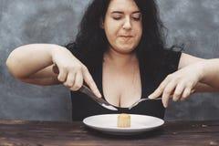 在吃松饼的食物的肥胖饥饿的妇女突袭 图库摄影