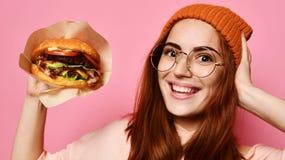 在吃汉堡包的夏天明亮的行家牛仔裤布料的滑稽的微笑的美好的年轻女人模型 图库摄影