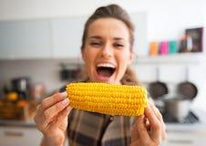 在吃煮沸的玉米的少妇的特写镜头 免版税库存照片