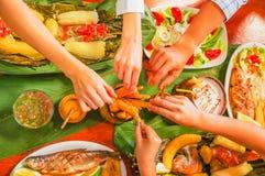 在吃被分类的食物的观点的人上,烤肉用土豆,甜蕃茄,沙拉,胡椒,油煎了大蕉 库存照片