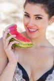 在吃西瓜的海滩的深色的模型 免版税库存照片