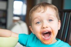 在吃饭的客人以后的愉快的矮小的男婴 免版税库存照片