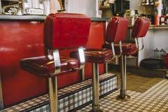 在吃饭的客人的红色摊凳子 免版税库存照片
