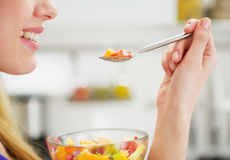 在吃水果沙拉的愉快的少妇的特写镜头 库存照片