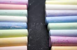 在各种各样的颜色的白垩在黑背景 库存图片