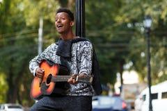 在吉他扮演的年轻音乐家,在好日子唱一首歌曲,在被弄脏的街道背景 库存图片