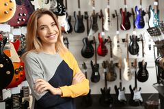 在吉他附近的年轻售货员在商店 图库摄影