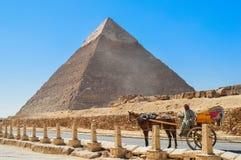 在吉萨棉金字塔的马无盖货车 免版税库存图片
