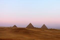 在吉萨棉高原的伟大的金字塔在黄昏 免版税库存图片