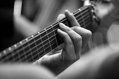 在吉他特写镜头的串的音乐家的手指 库存照片
