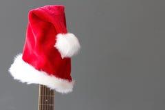 在吉他的红色圣诞节帽子有灰色背景 库存图片