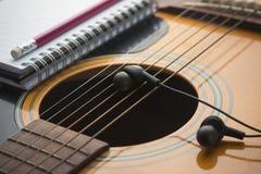 在吉他的耳机 免版税库存图片