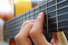 在吉他fretboard的手 库存照片
