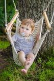 在吊床摇摆的小的逗人喜爱的男婴骑马在公园 免版税库存照片