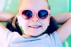 在吊床的一个年轻愉快的女孩的特写镜头 免版税库存图片