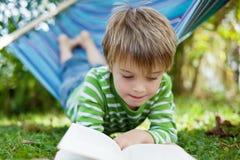在吊床的快乐的小男孩阅读书 免版税库存图片