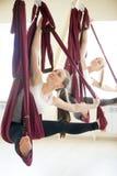 在吊床的旋转的座位角度瑜伽姿势 免版税库存图片