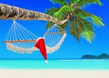 在吊床的红色圣诞老人帽子在棕榈群岛海滩 库存图片