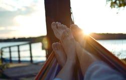 在吊床的脚在日落 免版税库存图片
