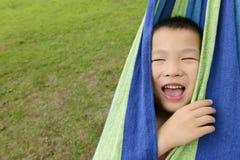 在吊床的逗人喜爱的孩子 免版税库存照片